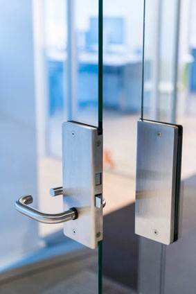 Glassdør i glassvegg med en solid dørlås og dørvrider i stål
